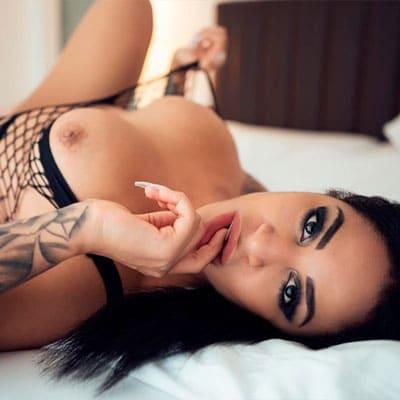 Junge Frau DirtyAkira mit nackten Titten auf dem Bett im Sexchat kennenlernen