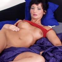 Heiße nackte Frau ganz allein im Bett